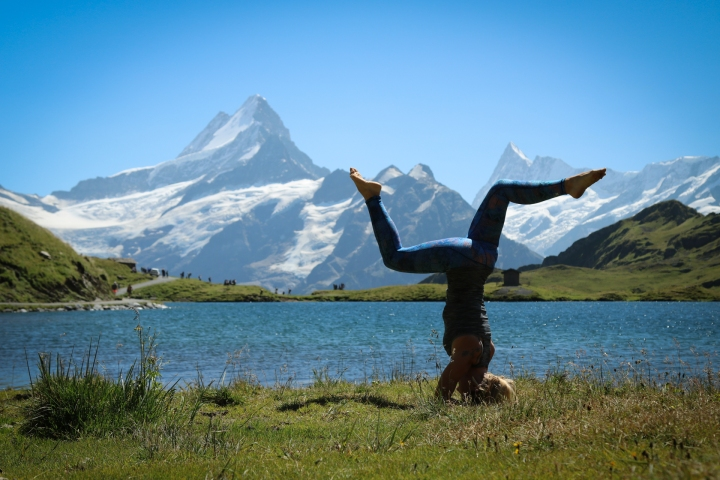 practicing yoga by a mountain lake in Grindelwald, Switzerland